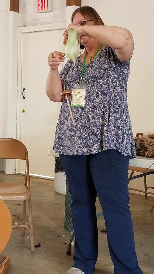 Patty demonstrates drop spinning with a Spanish Peacock spindle