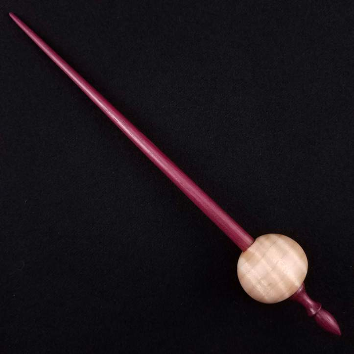 A Spanish Peacock pocket bead spindle featuring a tiger stripe maple whorl on a purpleheart shaft